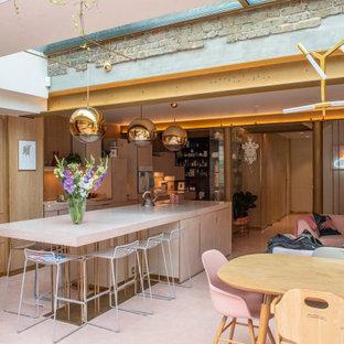Zweizeilige, Große Küche mit integriertem Waschbecken, flächenbündigen Schrankfronten, pinken Schränken, Betonarbeitsplatte, Küchenrückwand in Gelb, Elektrogeräten mit Frontblende, Betonboden, Kücheninsel, rosa Boden und rosa Arbeitsplatte in London