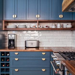 Offene, Kleine Klassische Küche in L-Form mit Einbauwaschbecken, Schrankfronten mit vertiefter Füllung, blauen Schränken, Arbeitsplatte aus Holz, Küchenrückwand in Weiß, Rückwand aus Keramikfliesen, Küchengeräten aus Edelstahl, braunem Holzboden, Halbinsel, braunem Boden und brauner Arbeitsplatte in Ottawa