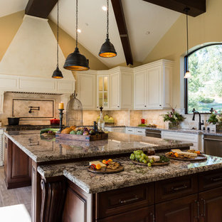 Mediterranean open concept kitchen inspiration - Inspiration for a mediterranean l-shaped beige floor open concept kitchen remodel in Los Angeles with raised-panel cabinets, white cabinets, granite countertops, beige backsplash, stone tile backsplash, stainless steel appliances and an island