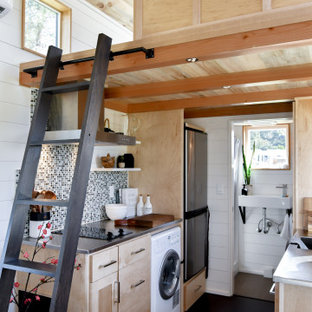This is an example of a small country galley open plan kitchen in Other with an integrated sink, shaker cabinets, light wood cabinets, stainless steel benchtops, green splashback, mosaic tile splashback, cork floors, no island, black floor, grey benchtop and wood.