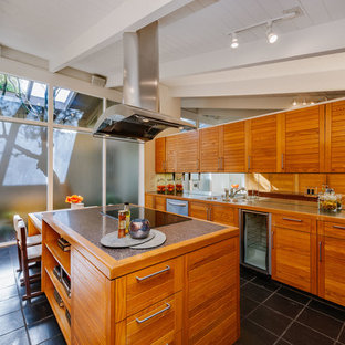 Mid-sized midcentury l-shaped eat-in kitchen in Los Angeles with stainless steel appliances, with island, grey floor, a double-bowl sink, louvered cabinets, medium wood cabinets, mirror splashback and cement tiles.
