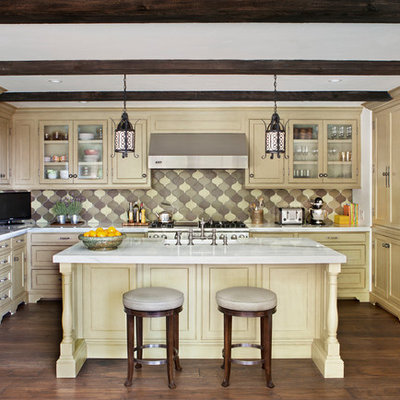 Kitchen - mediterranean l-shaped kitchen idea in Los Angeles with marble countertops, recessed-panel cabinets, yellow cabinets, multicolored backsplash and stainless steel appliances