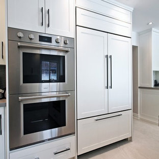 This is an example of a large contemporary u-shaped separate kitchen in Toronto with an undermount sink, shaker cabinets, white cabinets, marble benchtops, multi-coloured splashback, mosaic tile splashback, stainless steel appliances, marble floors, with island, beige floor and white benchtop.
