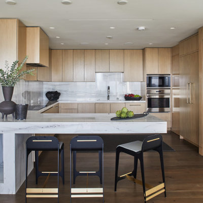 Example of a trendy u-shaped dark wood floor and brown floor kitchen design in Los Angeles with an undermount sink, flat-panel cabinets, white cabinets, white backsplash, stone slab backsplash, stainless steel appliances, a peninsula and white countertops