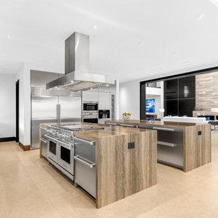 広いモダンスタイルのおしゃれなキッチン (ダブルシンク、フラットパネル扉のキャビネット、ステンレスキャビネット、大理石カウンター、シルバーの調理設備、磁器タイルの床、青い床、ベージュのキッチンカウンター) の写真
