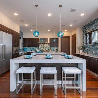 Immagine di una cucina a L tropicale con 2 o più isole, ante lisce, ante in legno bruno, paraspruzzi blu, paraspruzzi con piastrelle a listelli, elettrodomestici in acciaio inossidabile, pavimento in legno massello medio e top bianco