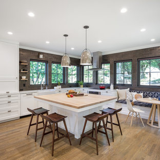 Inspiration for a transitional medium tone wood floor kitchen remodel in Portland with a farmhouse sink, shaker cabinets, white cabinets, metallic backsplash, subway tile backsplash, stainless steel appliances and an island