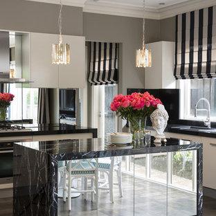 メルボルンの広いコンテンポラリースタイルのおしゃれなキッチン (ミラータイルのキッチンパネル、ダブルシンク、フラットパネル扉のキャビネット、ベージュのキャビネット、大理石カウンター、メタリックのキッチンパネル、シルバーの調理設備、濃色無垢フローリング、茶色い床) の写真
