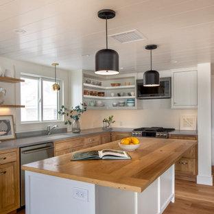 Idéer för att renovera ett litet vintage grå grått kök, med en undermonterad diskho, skåp i shakerstil, rostfria vitvaror, mellanmörkt trägolv, en köksö, brunt golv, bänkskiva i kvarts och grått stänkskydd