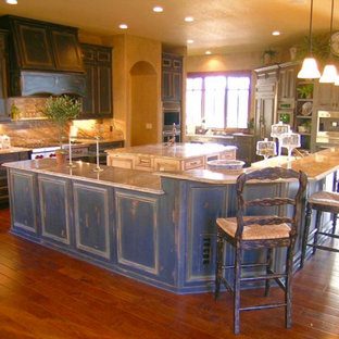 This is an example of a large u-shaped eat-in kitchen in Denver with an undermount sink, raised-panel cabinets, distressed cabinets, granite benchtops, beige splashback, slate splashback, stainless steel appliances, bamboo floors, multiple islands, brown floor and beige benchtop.