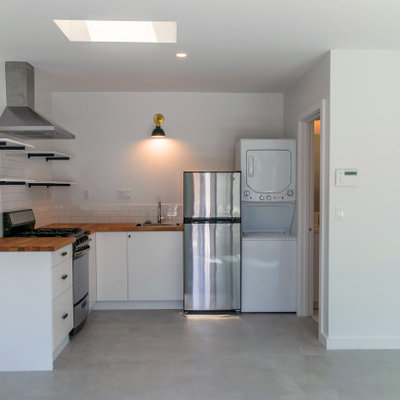 Inspiration for a small contemporary l-shaped concrete floor open concept kitchen remodel in Los Angeles with a single-bowl sink, flat-panel cabinets, white cabinets, wood countertops, white backsplash, ceramic backsplash, stainless steel appliances, no island and brown countertops