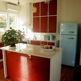 Inredning av ett 50 tals litet kök och matrum, med en enkel diskho, släta luckor, bänkskiva i kvarts, vitt stänkskydd, stänkskydd i sten, färgglada vitvaror, mellanmörkt trägolv och en köksö