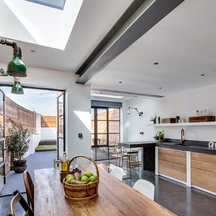 Medium sized contemporary l-shaped kitchen/diner in London with an integrated sink, flat-panel cabinets, medium wood cabinets, concrete worktops, black splashback, cement tile splashback, integrated appliances, concrete flooring and a breakfast bar.
