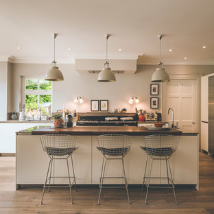 Medium sized contemporary kitchen in Other with flat-panel cabinets, beige cabinets, stainless steel appliances, medium hardwood flooring, an island and brown floors.