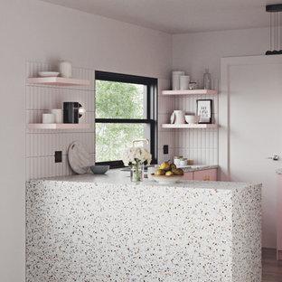 Modelo de cocina contemporánea con encimera de terrazo y armarios con paneles lisos