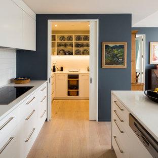 Exempel på ett mellanstort modernt parallellkök, med en undermonterad diskho, vita skåp, bänkskiva i kvarts, vitt stänkskydd, stänkskydd i porslinskakel, integrerade vitvaror, ljust trägolv, en köksö, släta luckor och brunt golv