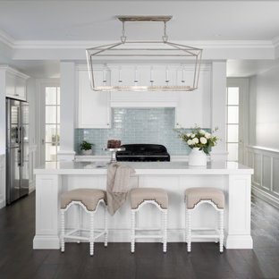 Inspiration for a mid-sized transitional l-shaped kitchen in Brisbane with a farmhouse sink, shaker cabinets, white cabinets, stainless steel appliances, brown floor and white benchtop.