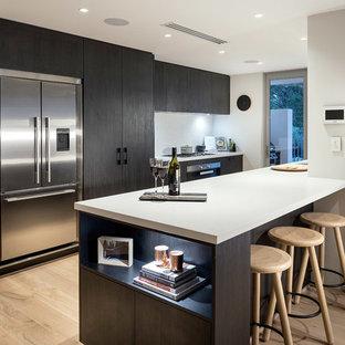 パース, WA, AUのII型コンテンポラリースタイルのペニンシュラキッチンの写真 (フラットパネル扉のキャビネット、濃色木目調キャビネット、シルバーの調理設備の、淡色無垢フローリング)