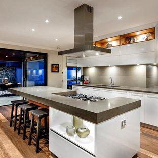 Foto på ett stort orientaliskt kök med öppen planlösning, med en undermonterad diskho, släta luckor, vita skåp, grått stänkskydd och en köksö
