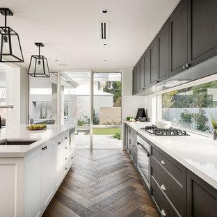 パースの大きいヴィクトリアン調のおしゃれなキッチン (アンダーカウンターシンク、黒いキャビネット、白いキッチンパネル、シルバーの調理設備の、濃色無垢フローリング) の写真