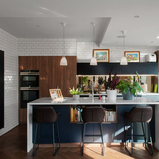 Design ideas for a medium sized contemporary l-shaped open plan kitchen in London with flat-panel cabinets, composite countertops, medium hardwood flooring, an island, white worktops, a submerged sink, medium wood cabinets, brown floors and mirror splashback.