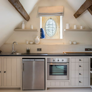 Inspiration for a small country l-shaped enclosed kitchen in Gloucestershire with a built-in sink, beige cabinets, beige splashback, stainless steel appliances, no island, beige floors and black worktops.