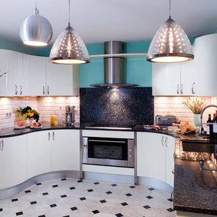 Cette image montre une cuisine ouverte design en U de taille moyenne avec des portes de placard blanches, un électroménager en acier inoxydable et aucun îlot.