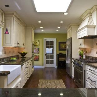 Foto de cocina ecléctica, cerrada, con electrodomésticos de acero inoxidable, fregadero sobremueble, armarios con paneles con relieve, puertas de armario beige y salpicadero de piedra caliza