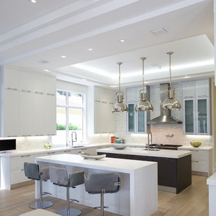 Design ideas for a large contemporary u-shaped eat-in kitchen in Miami with a single-bowl sink, glass-front cabinets, white cabinets, solid surface benchtops, grey splashback, stone tile splashback, panelled appliances, ceramic floors and multiple islands.