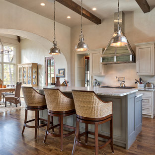 Photo of a mid-sized beach style galley eat-in kitchen in Other with beige cabinets, granite benchtops, beige splashback, dark hardwood floors, with island and recessed-panel cabinets.