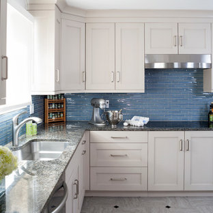 This is an example of a mid-sized transitional u-shaped kitchen in DC Metro with an undermount sink, recessed-panel cabinets, beige cabinets, granite benchtops, blue splashback, glass tile splashback, stainless steel appliances and linoleum floors.