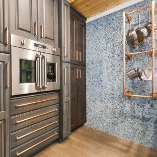 Idéer för att renovera ett litet eklektiskt vit vitt kök, med en rustik diskho, luckor med upphöjd panel, blå skåp, bänkskiva i koppar, blått stänkskydd, glaspanel som stänkskydd, rostfria vitvaror, bambugolv, en köksö och brunt golv