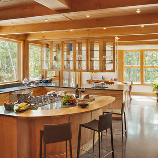 Contemporary eat-in kitchen pictures - Inspiration for a contemporary u-shaped concrete floor eat-in kitchen remodel in Portland Maine with an undermount sink, shaker cabinets, medium tone wood cabinets, solid surface countertops, stainless steel appliances and an island