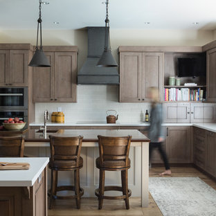 Mountain style l-shaped medium tone wood floor kitchen photo in Other with a single-bowl sink, recessed-panel cabinets, brown cabinets, gray backsplash, subway tile backsplash, stainless steel appliances, two islands and white countertops