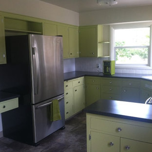 Design ideas for a mid-sized midcentury l-shaped separate kitchen in Portland with a drop-in sink, flat-panel cabinets, green cabinets, laminate benchtops, white splashback, ceramic splashback, stainless steel appliances, vinyl floors and a peninsula.