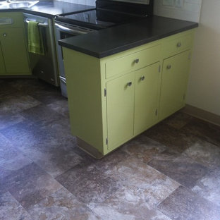 Mid-sized midcentury l-shaped separate kitchen in Portland with a drop-in sink, flat-panel cabinets, green cabinets, laminate benchtops, white splashback, ceramic splashback, stainless steel appliances, vinyl floors and a peninsula.