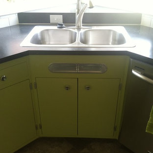 This is an example of a mid-sized midcentury l-shaped separate kitchen in Portland with a drop-in sink, flat-panel cabinets, green cabinets, laminate benchtops, white splashback, ceramic splashback, stainless steel appliances, vinyl floors and a peninsula.