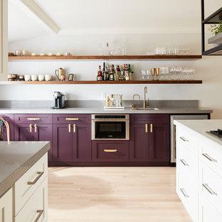 Modelo de cocina contemporánea con armarios estilo shaker, puertas de armario violetas, electrodomésticos de acero inoxidable, suelo de madera clara y suelo beige