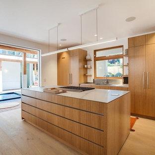 ロサンゼルスの大きいアジアンスタイルのおしゃれなキッチン (アンダーカウンターシンク、フラットパネル扉のキャビネット、中間色木目調キャビネット、クオーツストーンカウンター、メタリックのキッチンパネル、ガラスまたは窓のキッチンパネル、シルバーの調理設備の、淡色無垢フローリング、茶色い床、グレーのキッチンカウンター) の写真