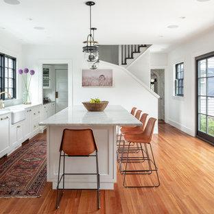 Inspiration pour une cuisine rustique avec un îlot central, un évier de ferme, un placard à porte shaker, des portes de placard blanches, un électroménager en acier inoxydable, un sol en bois brun et un plan de travail gris.