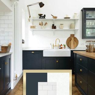 ダラスの中サイズのモダンスタイルのおしゃれなキッチン (ダブルシンク、シェーカースタイル扉のキャビネット、青いキャビネット、御影石カウンター、白いキッチンパネル、セラミックタイルのキッチンパネル、シルバーの調理設備の、淡色無垢フローリング、茶色い床、マルチカラーのキッチンカウンター) の写真