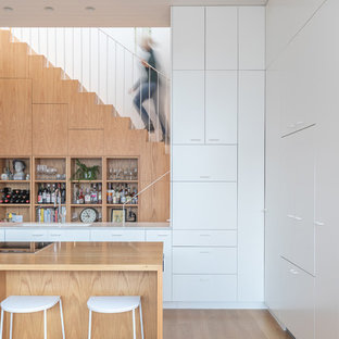 Small contemporary galley kitchen in Melbourne with an undermount sink, recessed-panel cabinets, white cabinets, black appliances, light hardwood floors, multiple islands, brown floor and multi-coloured benchtop.