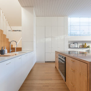 Inspiration for a small contemporary galley kitchen in Melbourne with an undermount sink, recessed-panel cabinets, white cabinets, black appliances, light hardwood floors, multiple islands, brown floor and multi-coloured benchtop.
