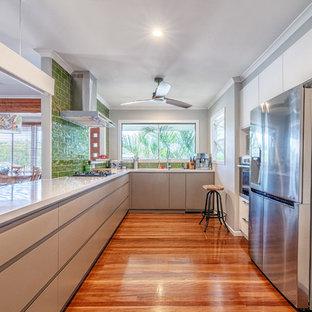 Large contemporary u-shaped kitchen in Brisbane with flat-panel cabinets, beige cabinets, green splashback, ceramic splashback, stainless steel appliances, medium hardwood floors, a peninsula, brown floor and white benchtop.