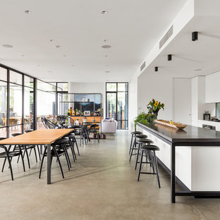 Inspiration for a contemporary galley open plan kitchen in Melbourne with flat-panel cabinets, white cabinets, window splashback, stainless steel appliances, concrete floors, with island, grey floor and grey benchtop.