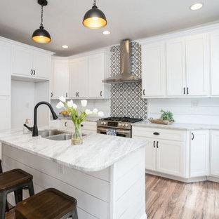 セントルイスの中くらいのカントリー風おしゃれなキッチン (ドロップインシンク、シェーカースタイル扉のキャビネット、白いキャビネット、大理石カウンター、白いキッチンパネル、塗装板のキッチンパネル、シルバーの調理設備、淡色無垢フローリング、茶色い床、グレーのキッチンカウンター、板張り天井) の写真