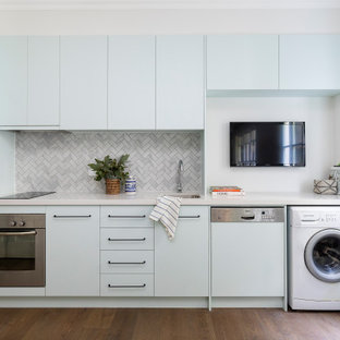 This is an example of a small contemporary single-wall kitchen in Brisbane with an undermount sink, quartz benchtops, grey splashback, marble splashback, no island, flat-panel cabinets, blue cabinets, brown floor and grey benchtop.