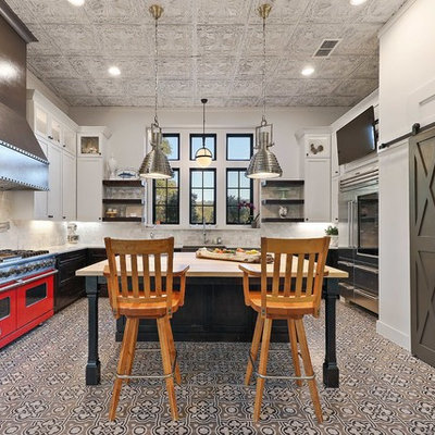 Example of a country u-shaped cement tile floor and multicolored floor kitchen design in Austin with shaker cabinets, black cabinets, white backsplash, stainless steel appliances, an island and white countertops