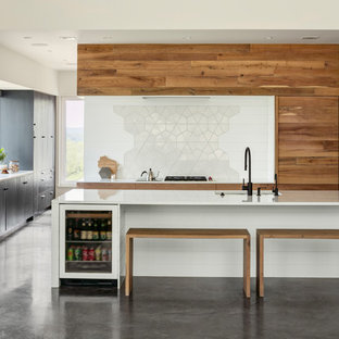 Modern kitchen ideas - Example of a minimalist l-shaped concrete floor and gray floor kitchen design in Other with an undermount sink, flat-panel cabinets, medium tone wood cabinets, white backsplash, black appliances, an island and white countertops