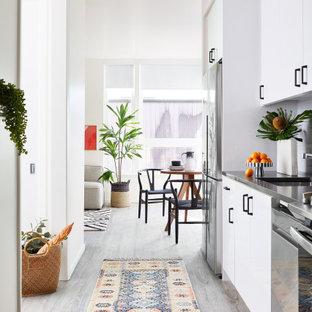 サンフランシスコの小さいコンテンポラリースタイルのおしゃれなキッチン (フラットパネル扉のキャビネット、白いキャビネット、珪岩カウンター、グレーのキッチンパネル、セラミックタイルのキッチンパネル、シルバーの調理設備、クッションフロア、アイランドなし、グレーの床、アンダーカウンターシンク、グレーのキッチンカウンター) の写真